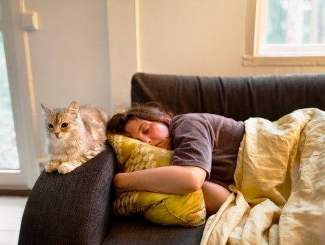 A woman sleeps on a couch with a cat perched on the armrest. Melatonin is a hormone that can help you sleep - but can it also give you nightmares?