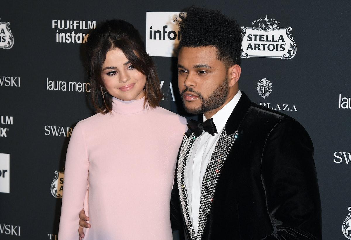 The Weekend wraps his arm around Selena Gomez on the red carpet.