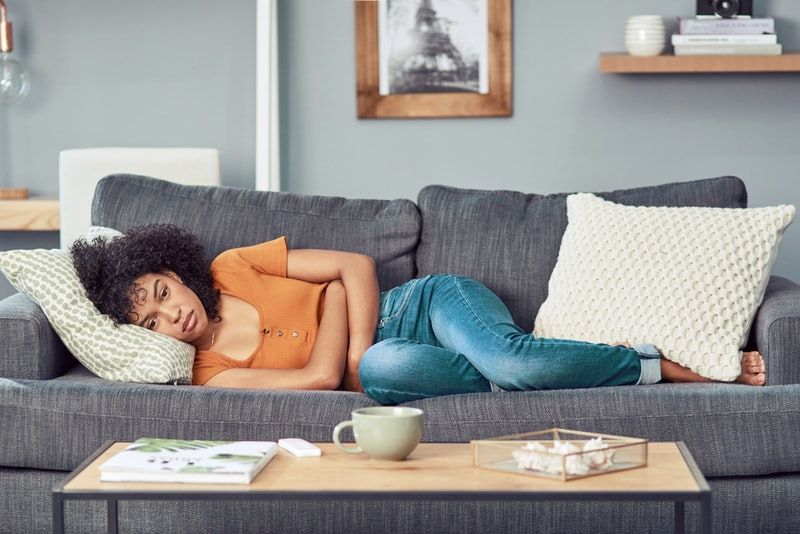 A person lays on her couch, hugging herself and staring into the distance. Muscle aches are common when you're stressed, even if you're not working out.