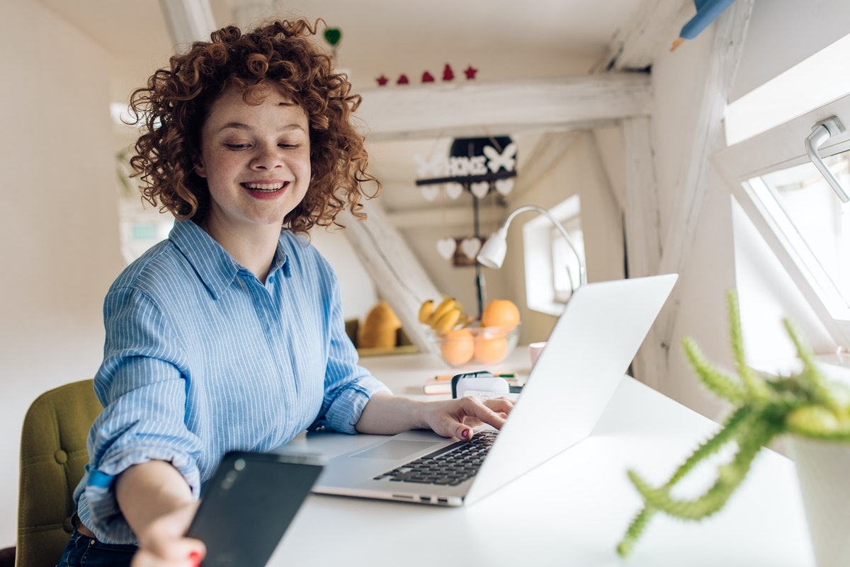 A woman wearing a striped blue and white button down looks at her phone and smiles while sitting at her desk in a bright room.