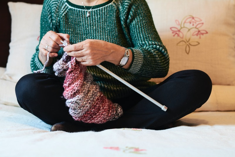 A woman knits a sweater. Any creative art practice can help your mental health, experts say