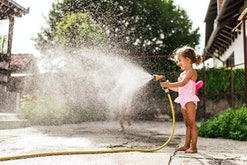 Playing with a water hose is a summer activity for kids at home.