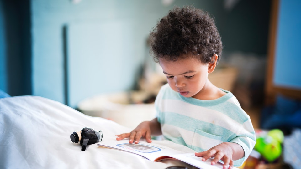 toddler boy looking at picture book in bedroom