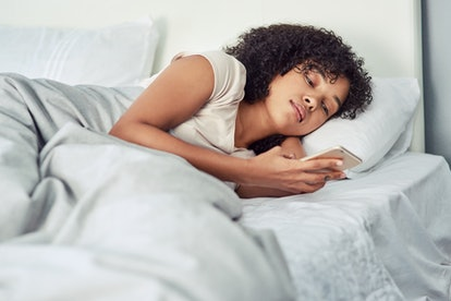 A woman looks at her phone in bed. Poor sleep can affect your cycle.