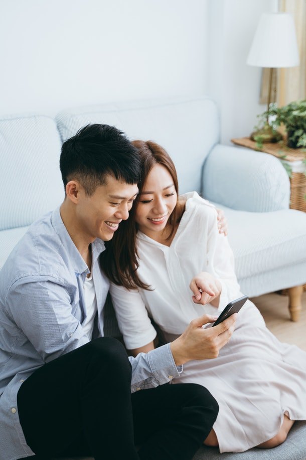 A young couple sits in their living room and smiles while on video chat with their friends.