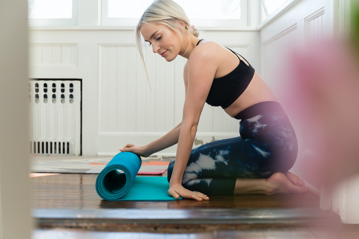 A young, blonde woman rolls out a blue yoga mat in her living room.