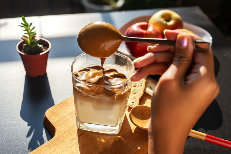 A woman spoons dalgona topping over milk. Making vegan dalgona coffee is actually pretty simple, so you can enjoy non-dairy dalgona coffee whenever you'd like.