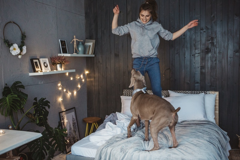 A woman tries a TikTok dance challenge in her bedroom, but is interrupted by her dog. TikTok dances are a good workout, experts say