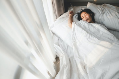 A woman sleeps in bed in the morning. If you find it hard to wake up in the morning, we asked a psychotherapists for tips to wake up in the morning.
