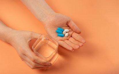 A woman holds several medications. Drugs including antipsychotics and birth control can affect periods.