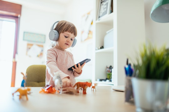 a little girl playing an iphone app
