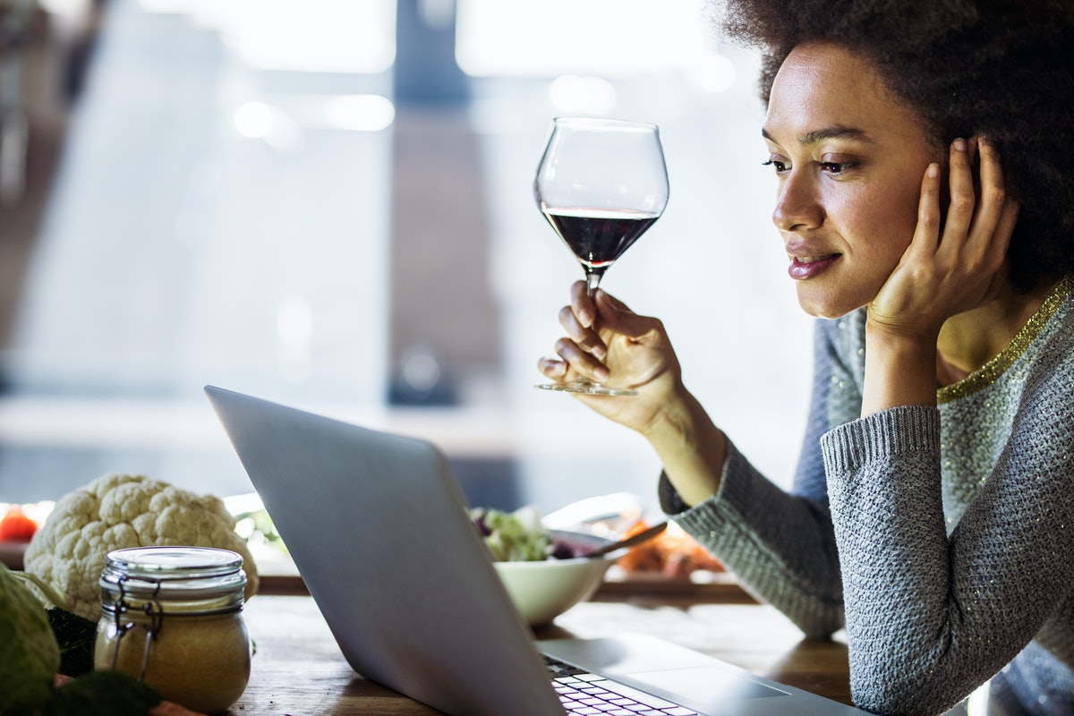 A woman sits at a kitchen table with her laptop and a glass of red wine.