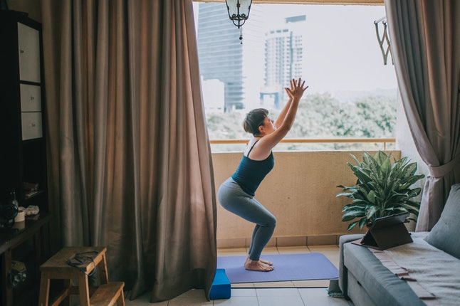 A woman does yoga on her balcony. Exercise in excess can disrupt periods.