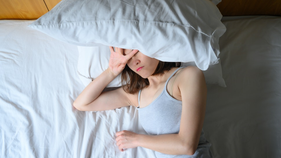 A woman is tired in bed with a pillow over her face. This article details 11 everyday things that can affect your period.