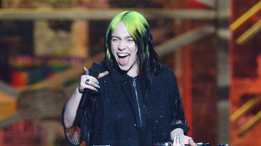 Billie EIlish accepts an award onstage.