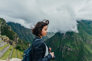A young woman stands in front of Machu Picchu in Peru with a camera around her neck.