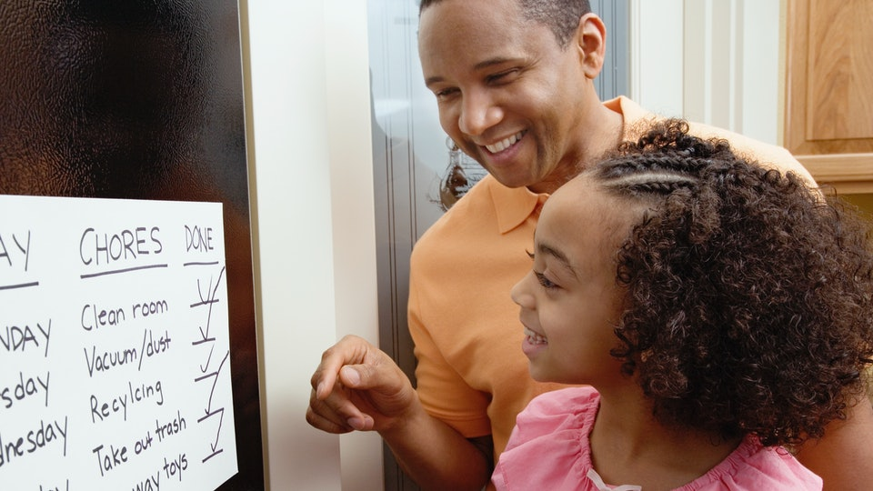 dad and daughter writing on chore chart