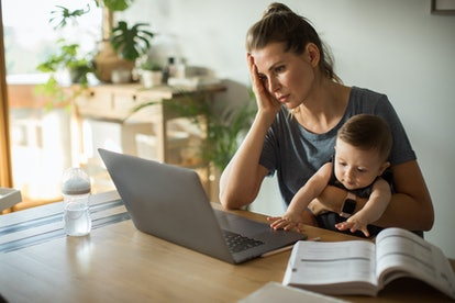 A person holds her baby at a table with a textbook propped open next to her laptop. The stress and anxiety associated with a global pandemic makes brain fog very understandable, but there are ways to help yourself think clearer and feel better.