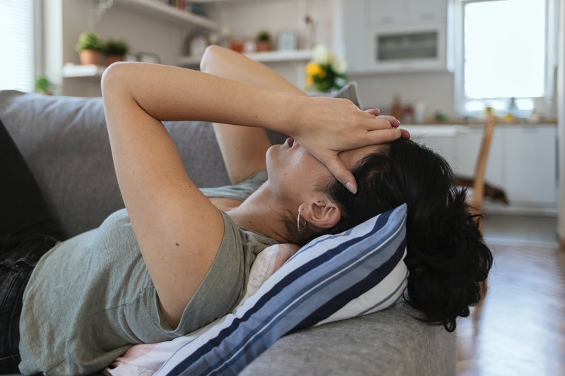 A person lays on her couch, propped up with pillows, with her head in her hands. If you're experiencing brain fog during the pandemic, it may be a symptom of COVID-19, but it is also likely to be a combination of stress and anxiety.