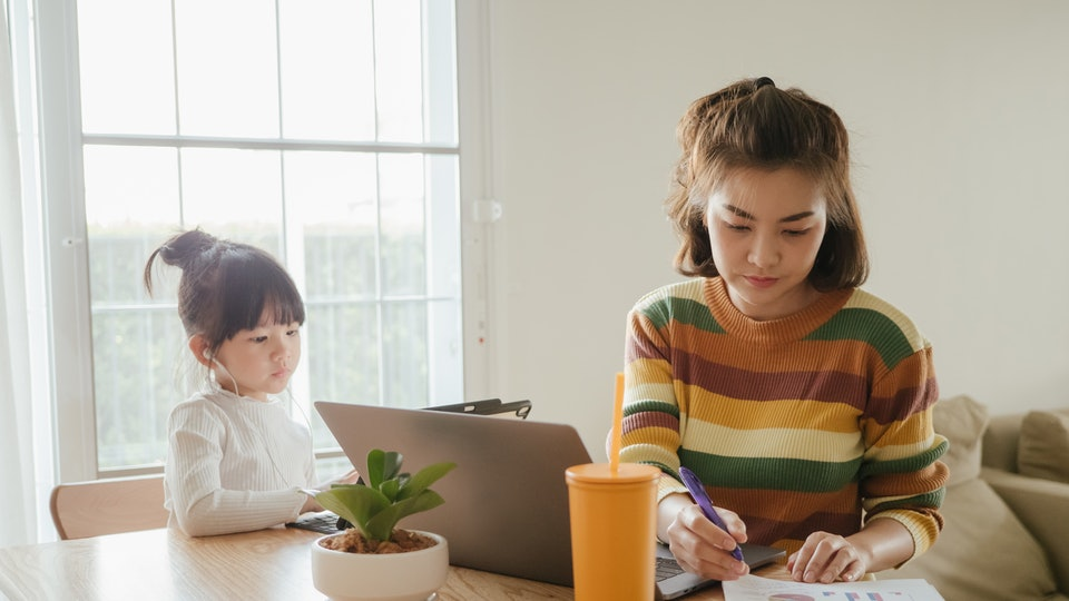 mother and daughter working on computers at table
