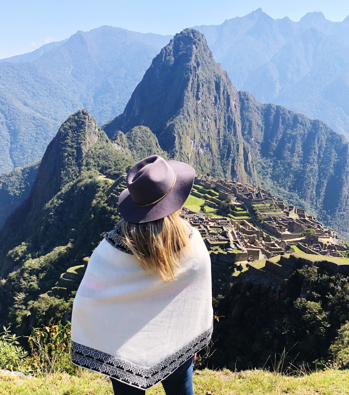 A young woman with blonde hair stands in front of Machu Picchu in Peru on a sunny day.