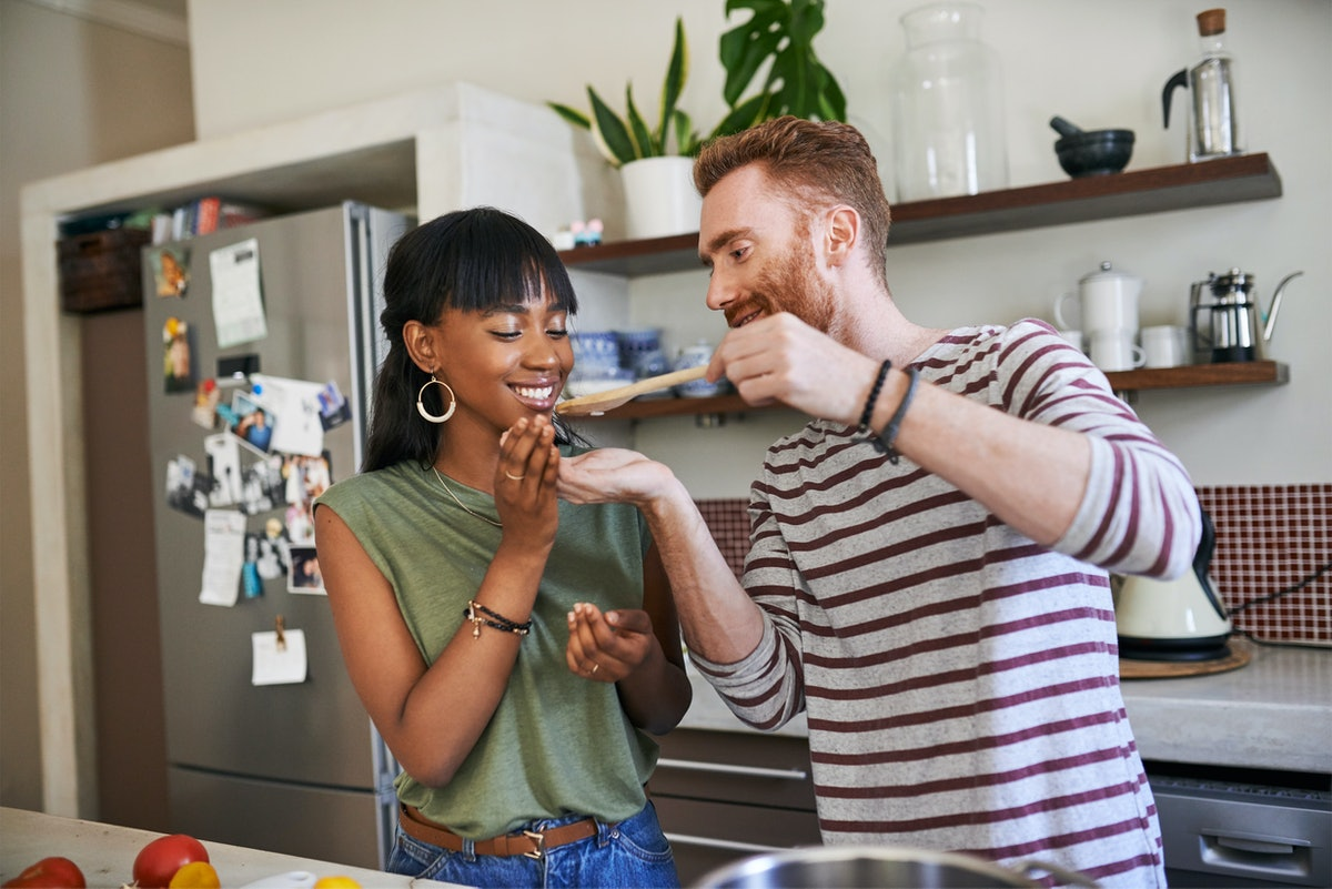 A young couple cooks in their kitchen and tries a spoonful of what they're making.