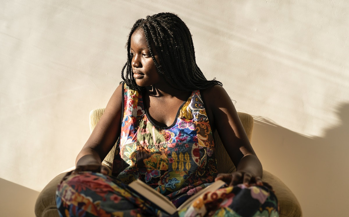 A young woman sits with a book in the sunlight.