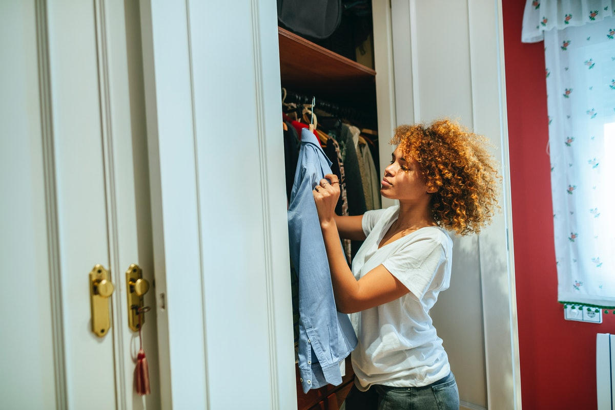 A young woman goes through the shirts in her closet.