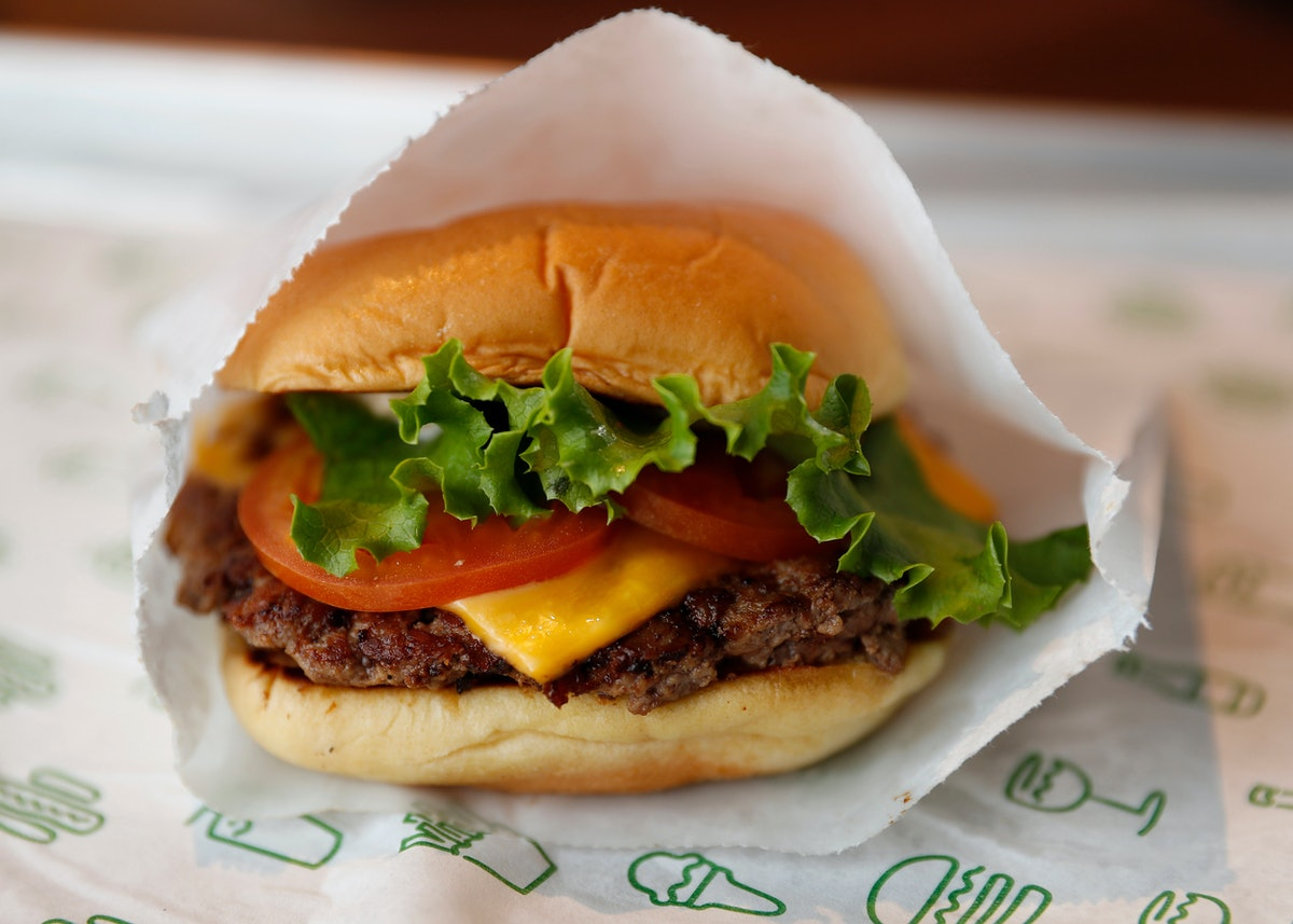 A Shake Shack burger sits on a tray with lettuce, tomato, and cheese, wrapped in paper.