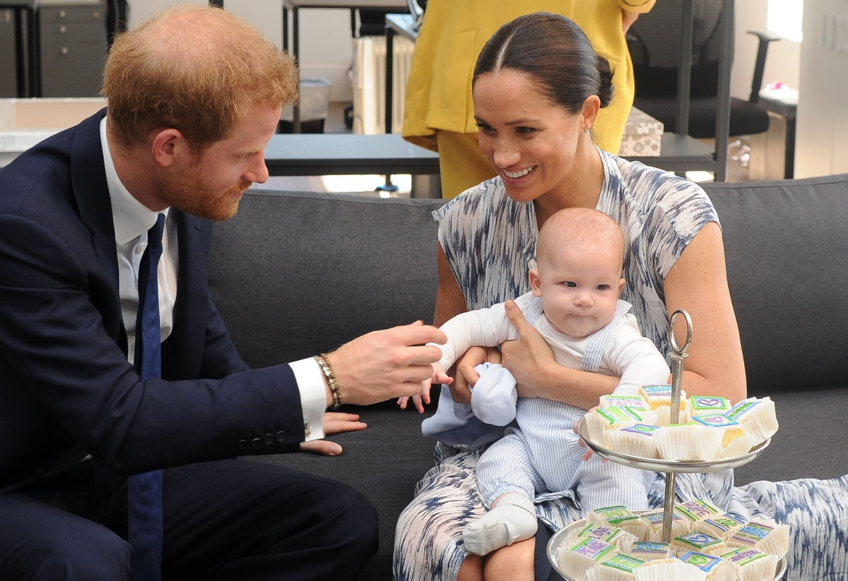 Prince Harry holds baby Archie's hand.