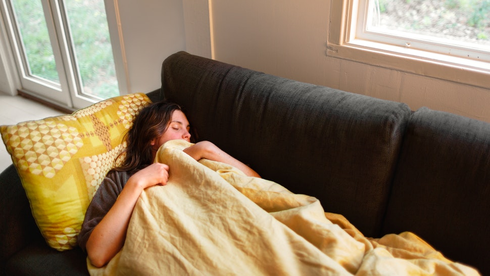 A woman takes a nap on a couch under a yellow blanket. If PMS or your period make you unusually tired, we asked doctors about what to do.