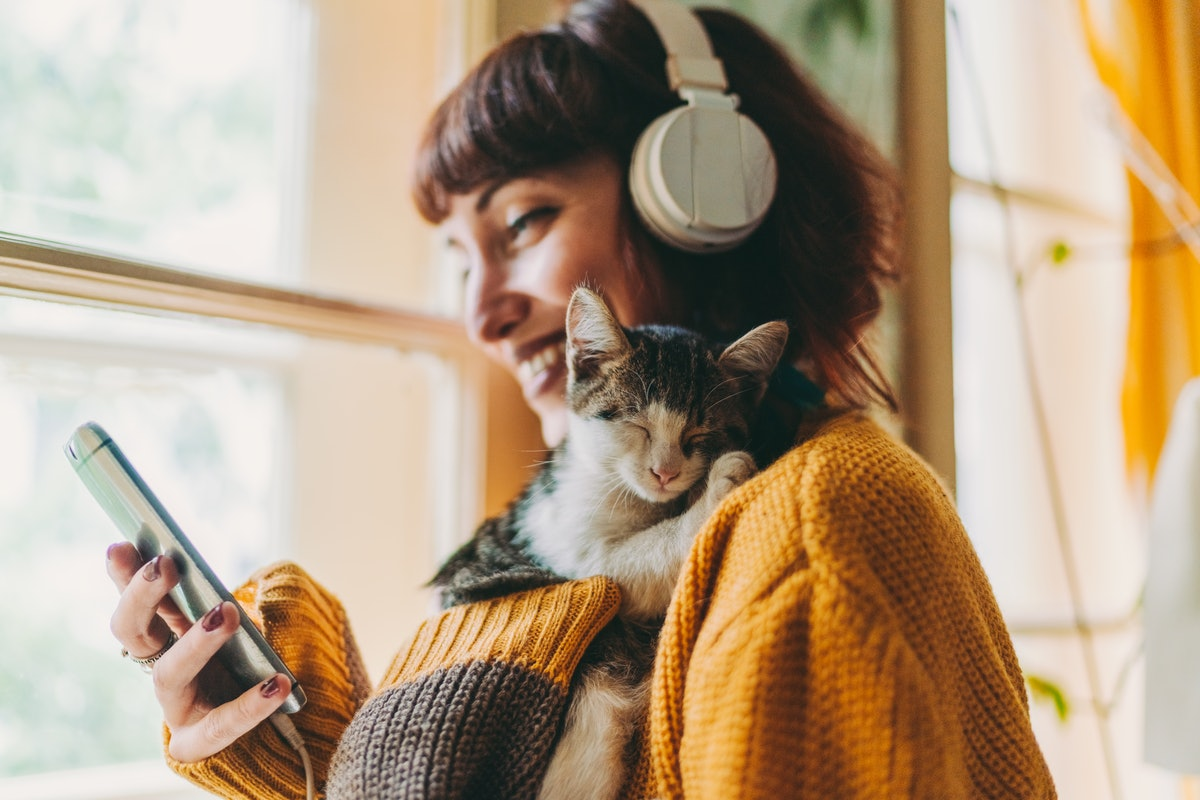 A young woman smiles while looking at her phone and holding a kitten.