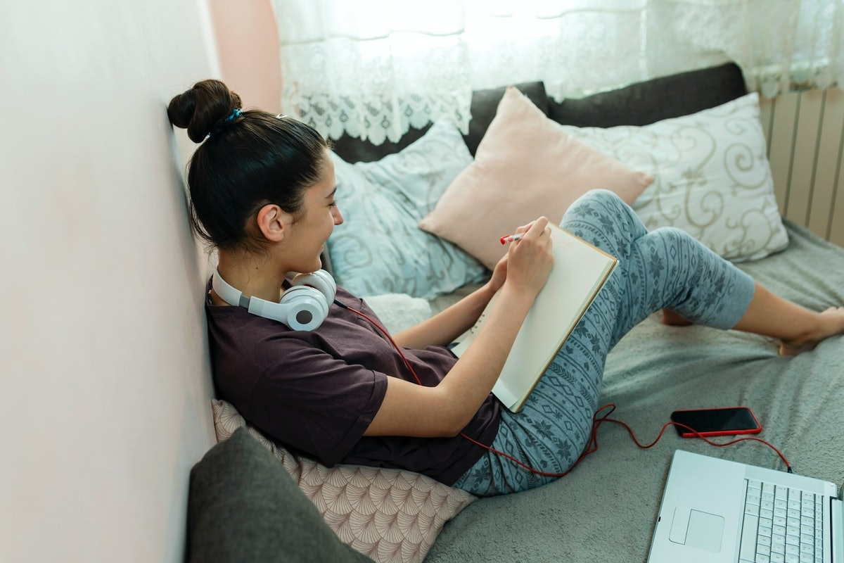 A young woman sits in her bed and draws a picture on a notepad while on video chat.
