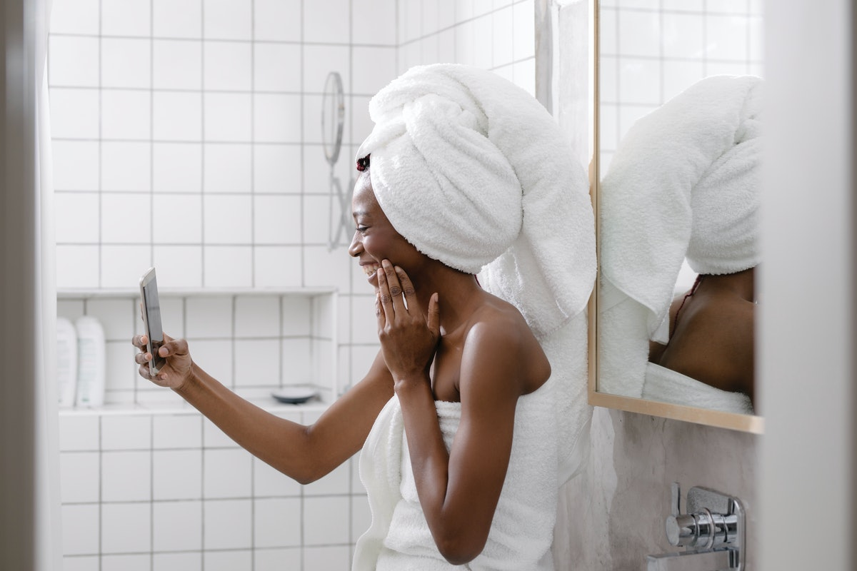 A young woman smiles in a towel while on video chat with her family.