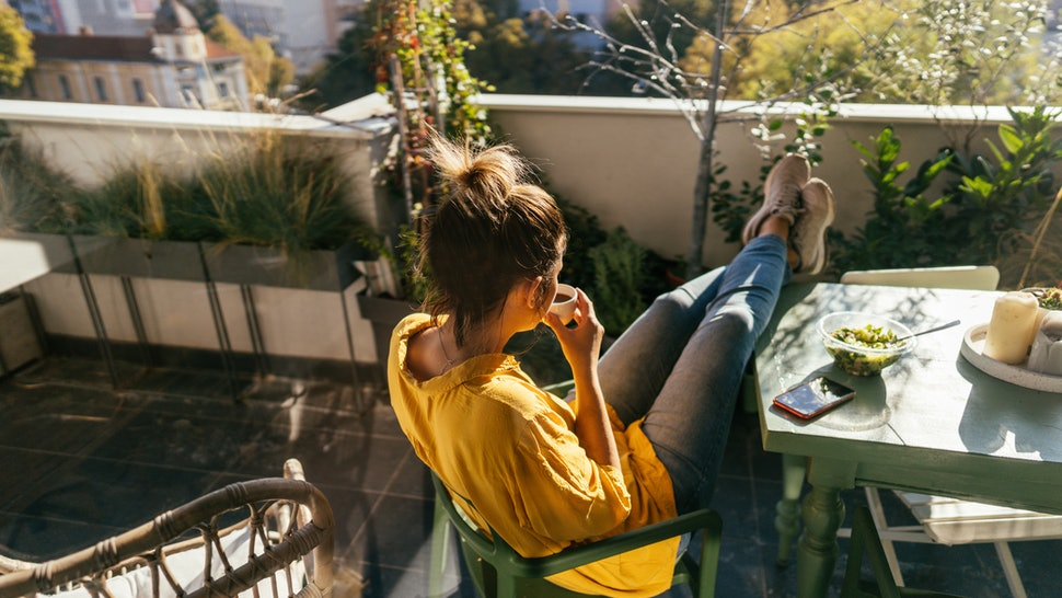 A woman drinks coffee with her feet up on a balcony These things can happen to your body when you mix marijuana & caffeine.