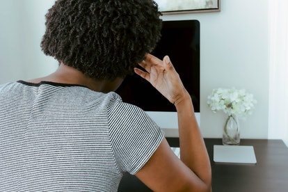 A woman looks at a screen with a headache. Screen time can increase headaches, because of glare, eye strain and posture.
