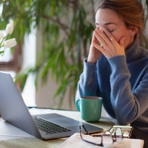 A woman rubs here eyes while on her computer. Coronavirus quarantine and increased screen time may be increasing eye strain, experts say.