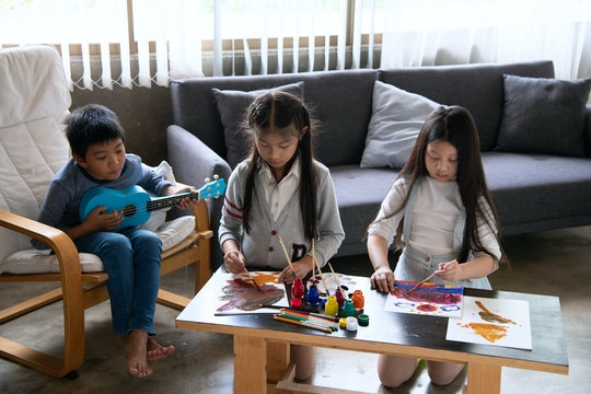 siblings doing art and music in living room