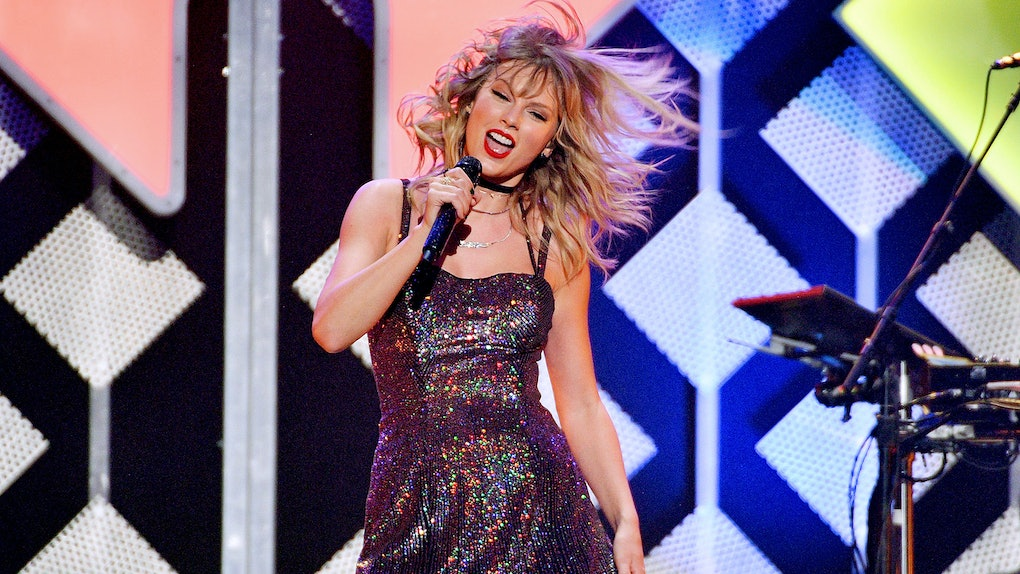 Taylor Swift sings and performs in a sparkly dress and boots.