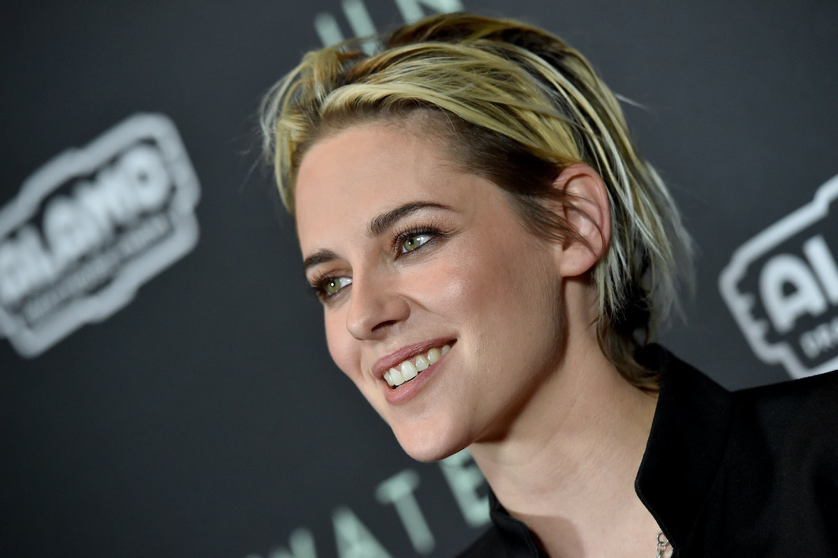 Kristen Stewart smiles on a red carpet with a messy, choppy, short pixie cut