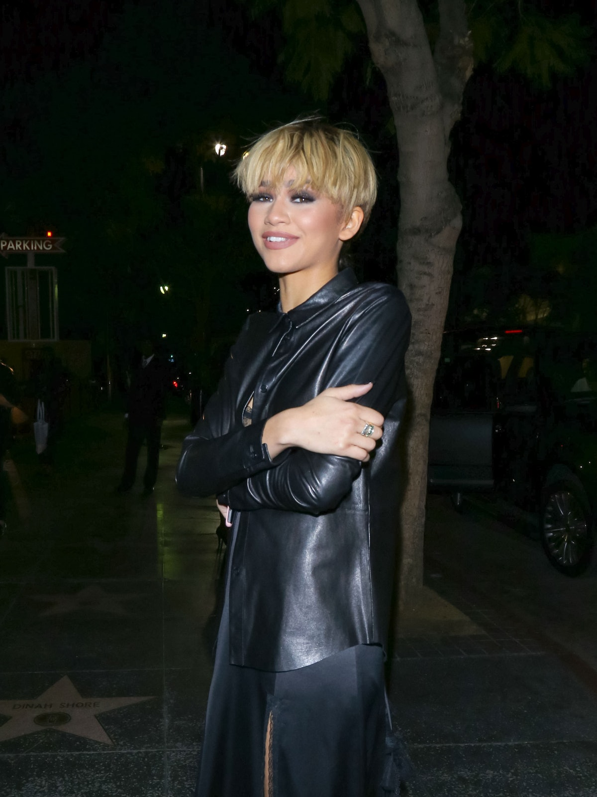 Zendaya stands with folded arms in a leather shirt with her hair cut into a short, pixie bowl cut, one of the cutest short haircuts