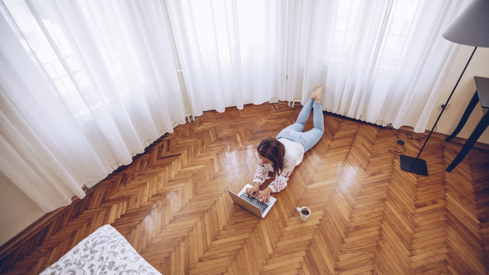 A woman does work on her computer while lying on the floor. If you feel stressed, it's worth knowing the difference between toxic stress and stress for your long-term health.