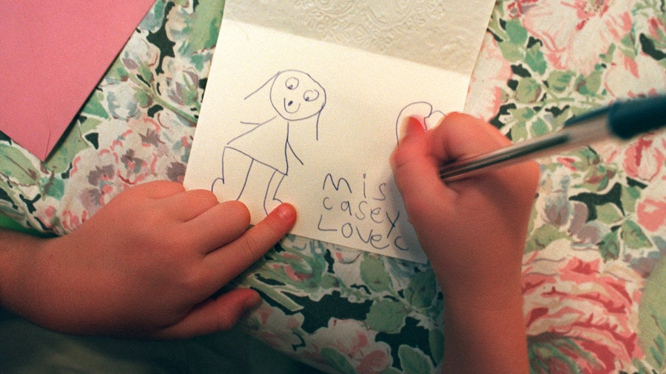 a child's hands writing a note to teacher