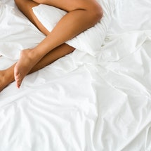 A woman's legs, lying in a bed with white sheets. Can I Have Sex After I've Had An Abortion? Experts and people who've been there weigh in.