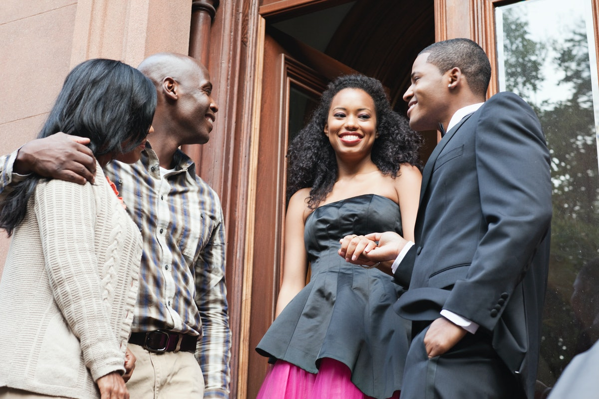 A young woman is dressed up for her at-home prom celebration with her family.