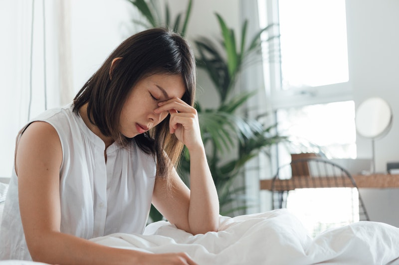 A woman with bed with a headache. Migraines appear most commonly in the mornings, according to specialists.