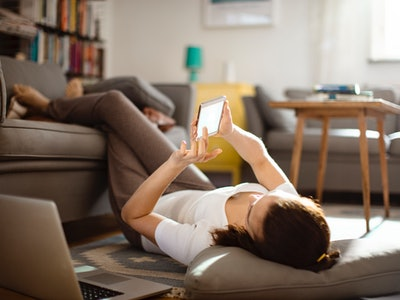 woman lying down in living room, looking at her phone