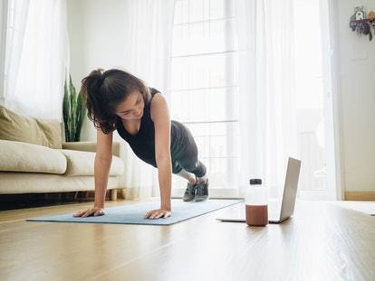 A person holds a plank in her living room while getting guidance from a video on her laptop. YouTube can be very helpful for teaching you the moves to beginning your first stretch routine.