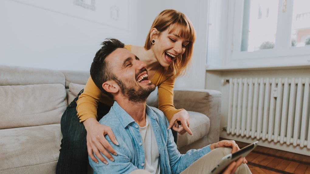 A young couple laughs while holding an iPad and hanging out in their cozy home.