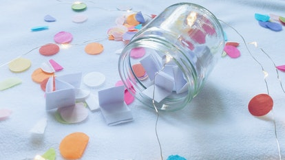 A mason jar is filled with folded paper and surrounded by string lights and confetti.